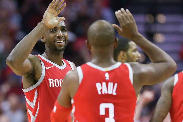 Houston Rockets forward Luc Mbah a Moute, left, celebrates with Chris Paul during a timeout during the second half of an NBA basketball game against the Denver Nuggets, Wednesday, Nov. 22, 2017, in Houston. Houston won the game 125-95. (AP Photo/Eric Christian Smith)