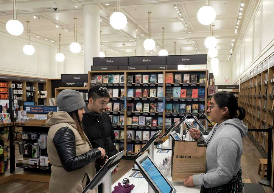 Customers buy a bag of books at an Amazon Books store, Monday, Nov. 20, 2017, in New York. Amazon goes into the holiday season with a newly magnified brick-and-mortar presence, giving it more opportunities to sell its Kindle e-readers, Fire tablets and other gadgets. The online retailer now has more than a dozen Amazon Books stores, which also sell toys, electronics and small gifts. (AP Photo/Mark Lennihan) Photo: Mark Lennihan, STF / Copyright 2017 The Associated Press. All rights reserved.