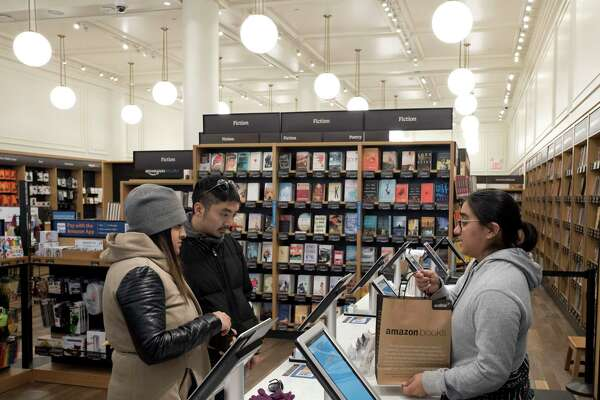 Customers buy a bag of books at an Amazon Books store, Monday, Nov. 20, 2017, in New York. Amazon goes into the holiday season with a newly magnified brick-and-mortar presence, giving it more opportunities to sell its Kindle e-readers, Fire tablets and other gadgets. The online retailer now has more than a dozen Amazon Books stores, which also sell toys, electronics and small gifts. (AP Photo/Mark Lennihan)