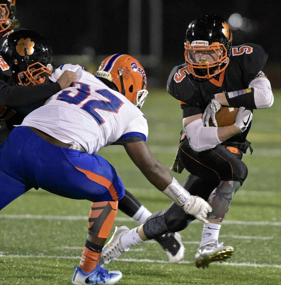 Ridgefield's Benjamin Seward (5) cuts across the path of Danbury's Solomon James (32) in the football game between Danbury and Ridgefield high schools on Wednesday night, November 22, 2017, at Ridgefield High School, in Ridgefield, Conn. Photo: H John Voorhees III / Hearst Connecticut Media / The News-Times