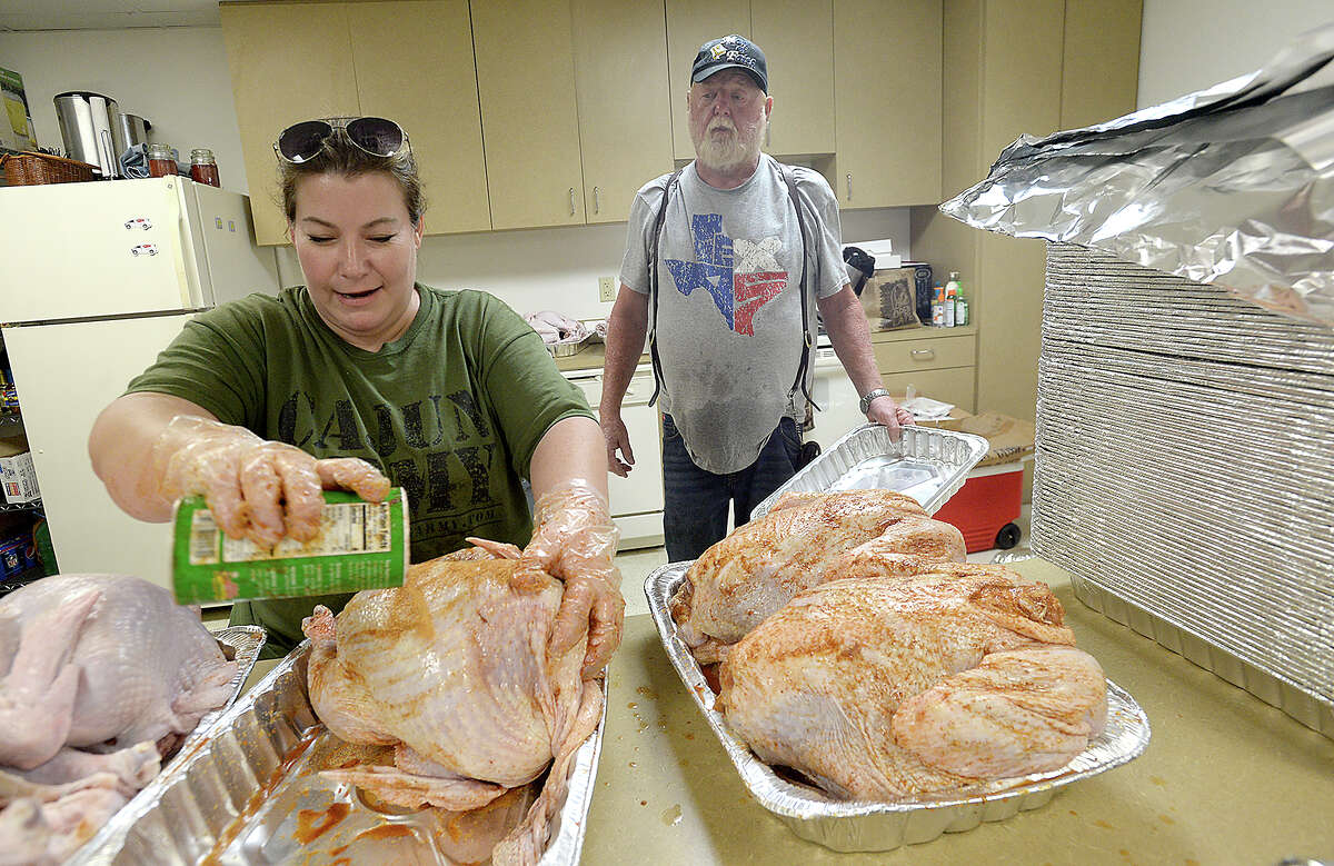 Tom Posey and volunteer helper Alison Duplessis, a Louisiana resident and member of the Cajun Army since 2016, talk as they prep the 100 turkeys which they will serve up at the Red Cross in Orange on Thaksgiving Day. Posey, who owns a food truck and produce stand in Orange, has been putting his years of cooking expertise to work, serving over 40,000 meals to those in need in the wake of Tropical Storm Harvey. Posey, with the aid of the Cajun Army, Red Cross and other volunteers, expects to offer their holiday feast to nearly 2,000 people. The Red Cross has opened its kitchen facilities and will have tents and seating set up at their office at 3901 I-10 eastbound. In addition to turkey, volunteers will be serving chicken, ham, and an array of traditional side dishes. Photo taken Wednesday, November 22, 2017 Kim Brent/The Enterprise