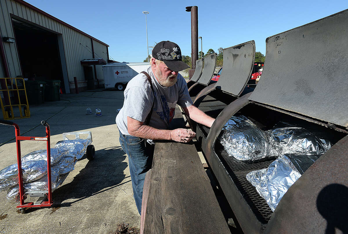 Tom Posey hauls out the first batch of the 100 seasoned turkeys to the outdoor barbecue pits in preparation for the Thanksgiving Day feast he and volunteers with the Cajun Army will serve at the Red Cross facility in Orange. Posey, who owns a food truck and produce stand in Orange, has been putting his years of cooking expertise to work, serving over 40,000 meals to those in need in the wake of Tropical Storm Harvey. Posey, with the aid of the Cajun Army, Red Cross and other volunteers, expects to offer their holiday feast to nearly 2,000 people. The Red Cross has opened its kitchen facilities and will have tents and seating set up at their office at 3901 I-10 eastbound. In addition to turkey, volunteers will be serving chicken, ham, and an array of traditional side dishes. Photo taken Wednesday, November 22, 2017 Kim Brent/The Enterprise