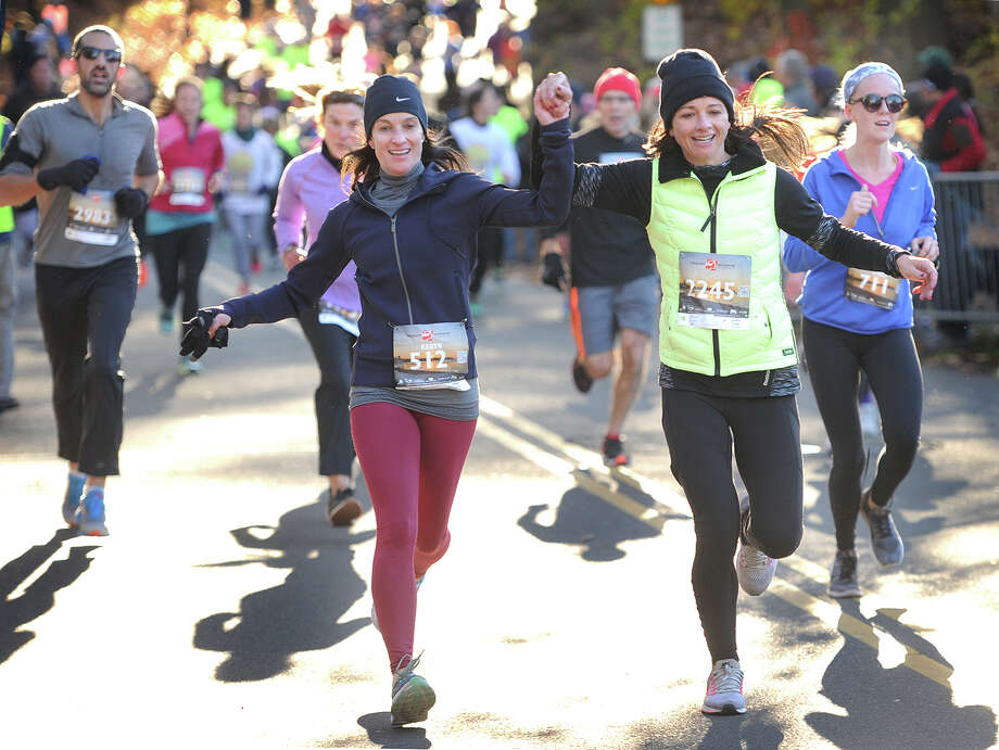 Friends Keryn Geller, left, of Westport, and Kristy Gordon, of Weston, grasp hands as the cross the finish line at the annual Pequot Runners 5-mile Thanksgiving Day Road Race in the Southport section of Fairfield, Conn. on Thursday, November 23, 2017. Over 4000 runners registered for this year's race. Photo: Brian A. Pounds, Hearst Connecticut Media / Connecticut Post