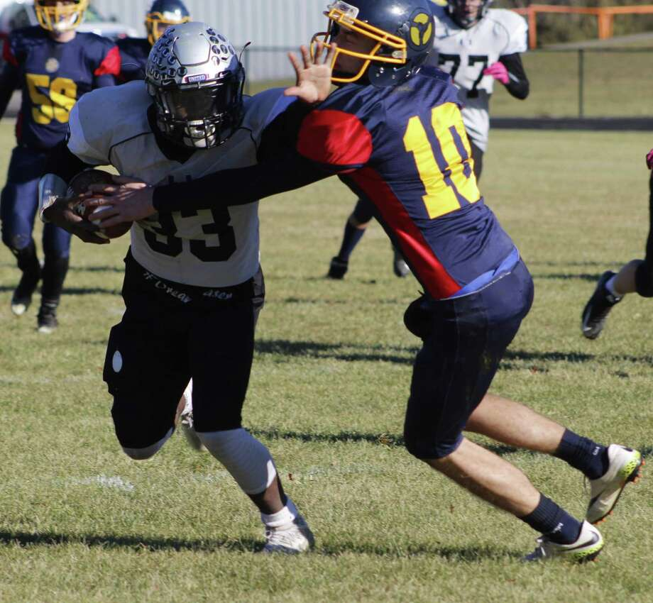 Abbott Tech/Immaculate's Jordan O'Brien, left, surges ahead for extra yardage as Christian Saade of Wolcott Tech/Housatonic/Wamogo tries to tackle him during the football game at Housatonic Valley Regional High School in Falls Village Nov. 23, 2017. Photo: Richard Gregory / Richard Gregory