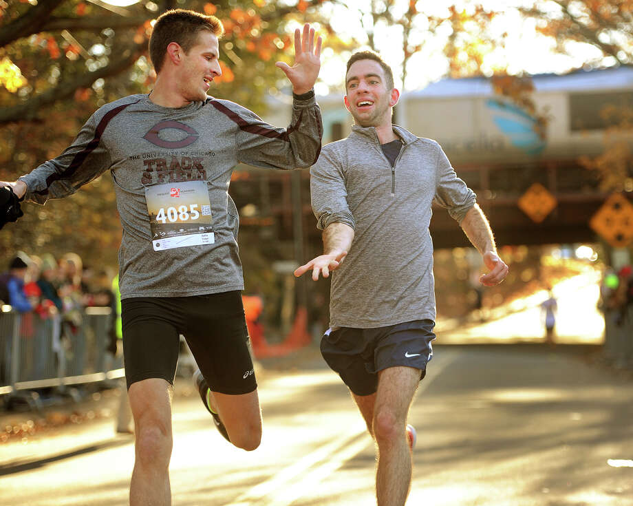 Friends Peter Kreuch, left, of Darien, and Aidan Fiol, of Fairfield, slap five as they cross the finish line at the annual Pequot Runners 5-mile Thanksgiving Day Road Race in Fairfield, Conn. on Thursday, November 23, 2017. Over 4000 runners registered for this year's race. Photo: Brian A. Pounds, Hearst Connecticut Media / Connecticut Post