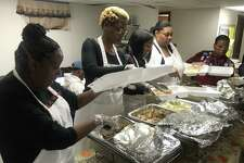 Volunteers prepare Thanksgiving meals at Church of God and Saints of Christ in New Haven on Thursday.