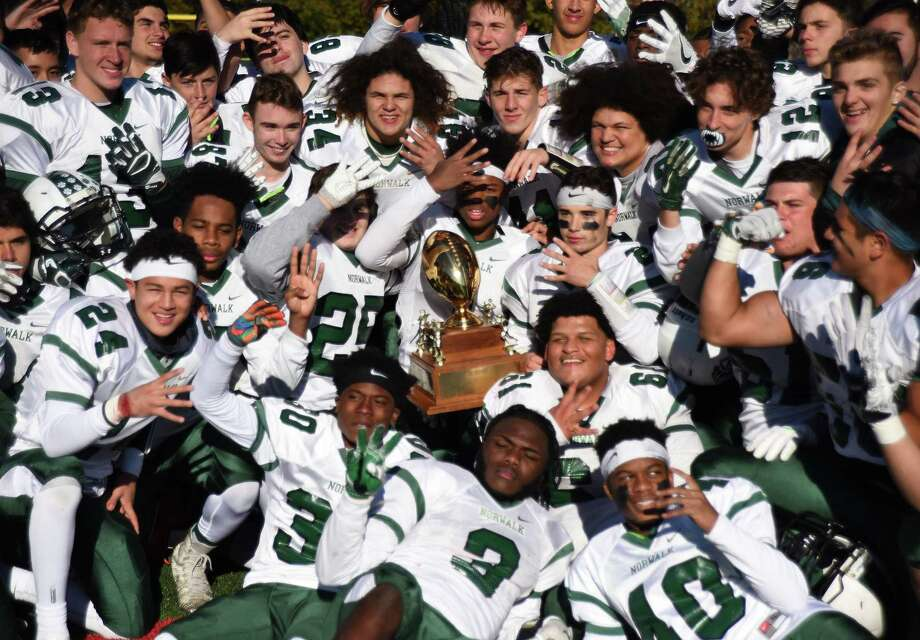 The Norwalk High football team celebrates with the Sam Testa Trophy after beating cross-city rival Brien McMahon by a 43-26 score on Thursday at Casagrande Field. Photo: John Nash / Hearst Connecticut Media / Norwalk Hour