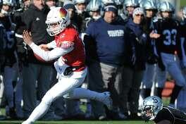 Greenwich quarterback Gavin Muir scrambles away from Staples linebacker Ben van der Merwe in Greenwich's 31-14 win over Staples on Thanksgiving Day at Staples High School in Westport.