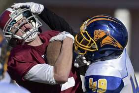 Bethel's Zack Perry (2) is brought down by Brookfield's Jihoon Kang (49) during a return after a safety in the Thanksgiving Day football game between Brookfield and Bethel high schools, on Thursday, November 23, 2017, at Bethel High School, in Bethel, Conn.