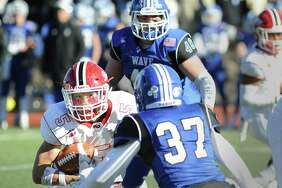New Canaan running back Owen Shin (#5), left, attempts to evade Darien defender Brandon Yarish (#37) on a running play during the 2017 Turkey Bowl high school football game between Darien High School and New Canaan High School at Boyle Stadium in Stamford, Conn., Thursday, Nov. 23, 2017. New Canaan won the game 27-0, beating an undefeated Darien team that was without starting quarterback Jack Joyce and star defensive back Brian Minicus, both of whom were arrested Wednesday night on charges stemming from an assault earlier in the month.