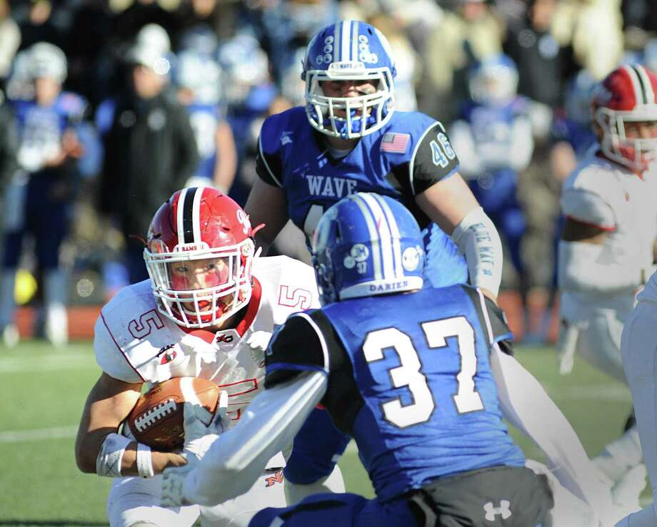 New Canaan running back Owen Shin attempts to evade Darien defender Brandon Yarish during the Rams' 27-0 victory on Thursday in the Turkey Bowl. Photo: Bob Luckey Jr. / Hearst Connecticut Media / Greenwich Time