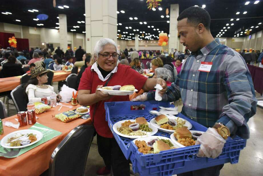Elizabeth Luna receives a plate of food during the 38th annual Raul Jimenez Thanksgiving Dinner at the Henry B. Gonzalez Convention Center on Thursday, Nov. 23, 2017. The event is named after a restauranteur and businessman who started the event in 1979. Organizers said 9,400 lbs. of turkey, 6,250 lbs. of stuffing and 25,000 dinner rolls were used for the 25,000 meals served, mostly to seniors. Photo: Billy Calzada /San Antonio Express-News / San Antonio Express-News
