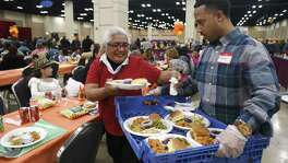 Elizabeth Luna receives a plate of food during the 38th annual Raul Jimenez Thanksgiving Dinner at the Henry B. Gonzalez Convention Center on Thursday, Nov. 23, 2017. The event is named after a restauranteur and businessman who started the event in 1979. Organizers said 9,400 lbs. of turkey, 6,250 lbs. of stuffing and 25,000 dinner rolls were used for the 25,000 meals served, mostly to seniors.