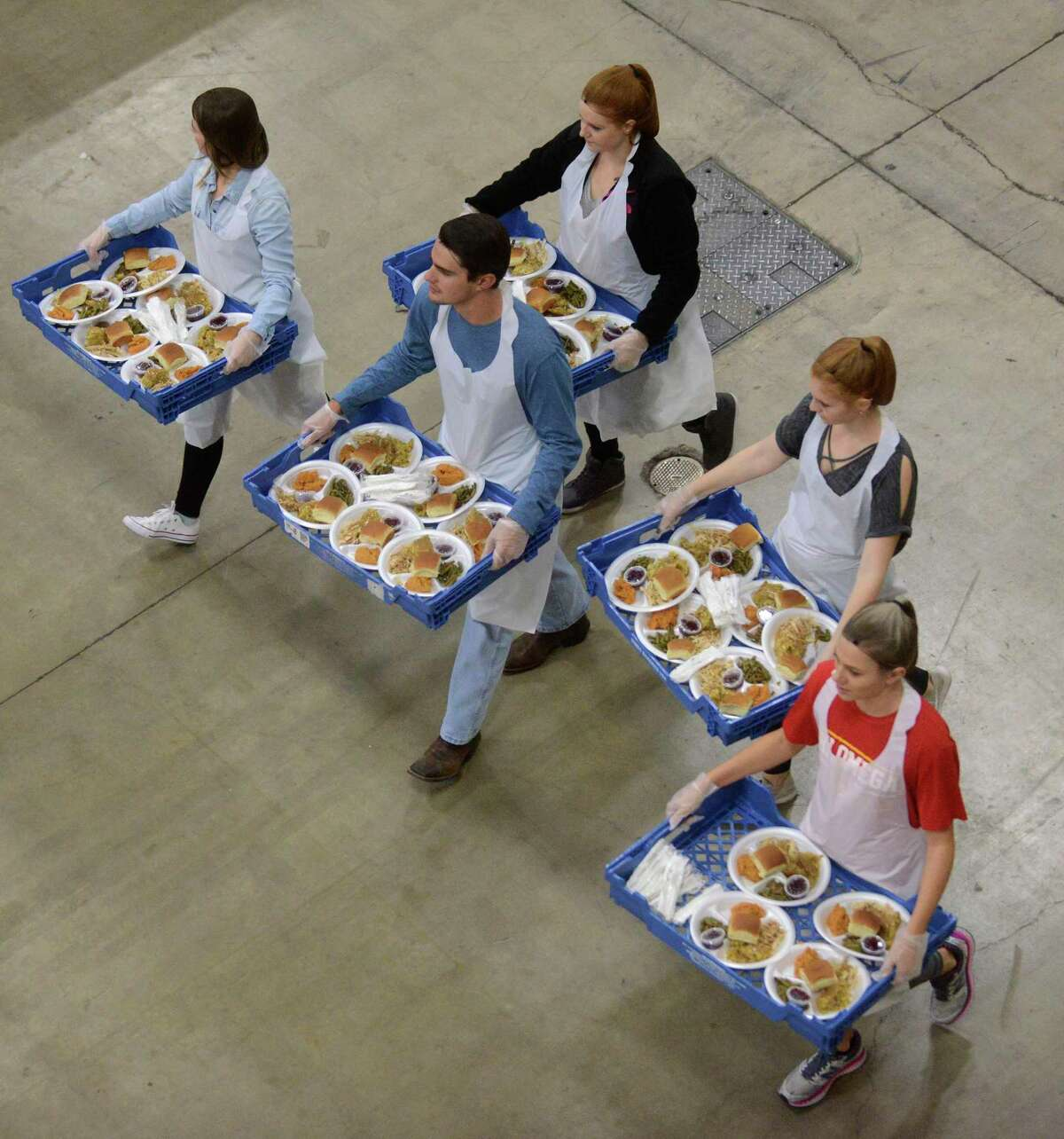 Volunteers carry plates at the Raul Jimenez Thanksgiving Dinner in 2017 at the Henry B. Gonzalez Convention Center.