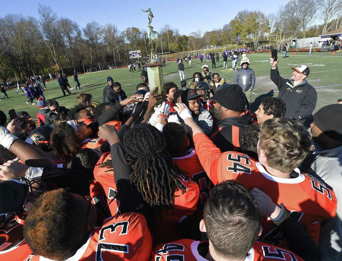 Stamford coach Jamar Greene hoists the Frank Robotti Trophy following the Black Knights 26-14 win over Westhill during a Thanksgiving Day football game at Westhill High School in Stamford, Conn. on Thursday, Nov. 23, 2017.