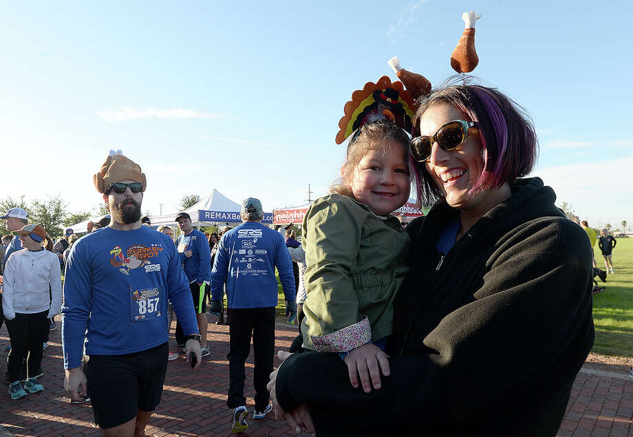 Carrie Laprocina cuddles with her daughter Kyler as they wait for the start of their 5K during the 27th annual Sea Rim Striders' Turkey Trot Thanksgiving morning in downtown Beaumont. The event this year benefits The Rainbow Room, which supplies emergency materials to aid neglected and abused children in the community. Photo taken Thursday, November 23, 2017 Kim Brent/The Enterprise Photo: Kim Brent / BEN