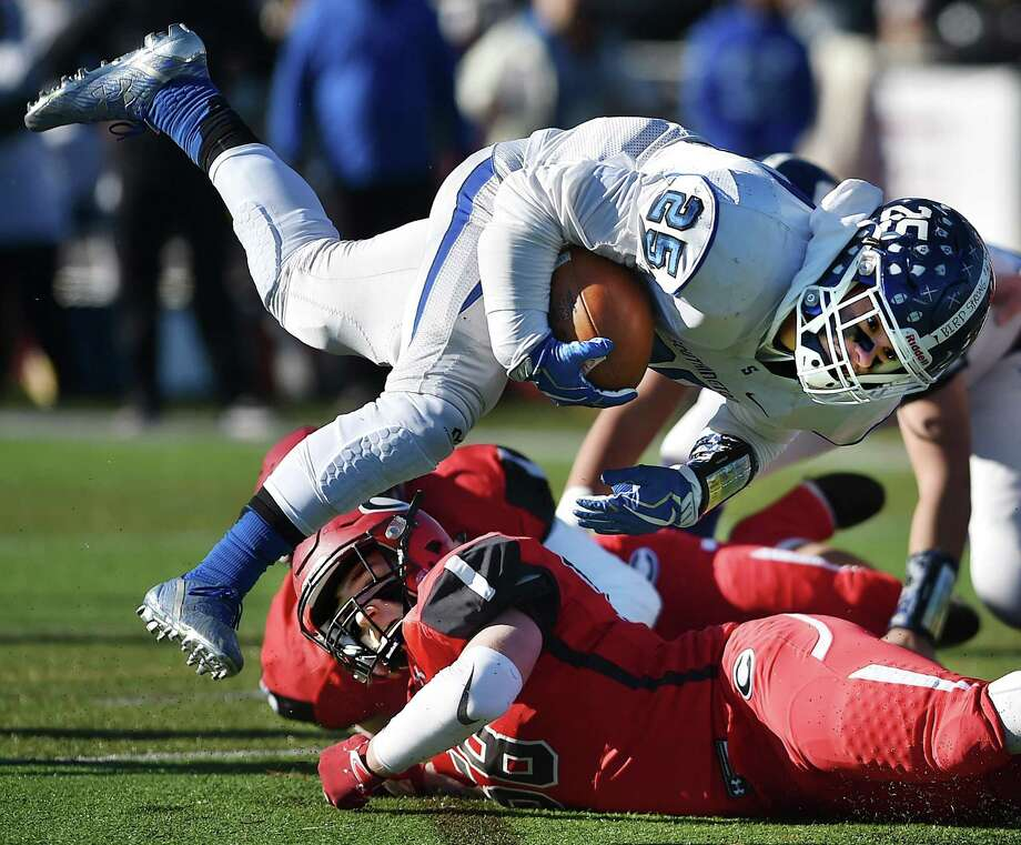 Southington running back Ryan Montalvo is tackled by Cheshire linebacker Nick Nelson on Thanksgiving Day, Thursday, Nov. 23, 2017, at Alumni Field at the David B. Maclary Athletic Complex at Cheshire High School. Southington won, 30-22. Photo: Catherine Avalone / Hearst Connecticut Media / New Haven Register