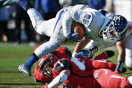 Southington running back Ryan Montalvo is tackled by Cheshire linebacker Nick Nelson on Thanksgiving Day, Thursday, Nov. 23, 2017, at Alumni Field at the David B. Maclary Athletic Complex at Cheshire High School. Southington won, 30-22.