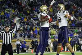 Navy wide receiver Craig Scott (82) celebrates a touchdown catch with Tyler Carmona (88) against Notre Dame during the second half of an NCAA college football game in South Bend, Ind., Saturday, Nov. 18, 2017. Notre Dame defeated Navy 24-17. (AP Photo/Michael Conroy)