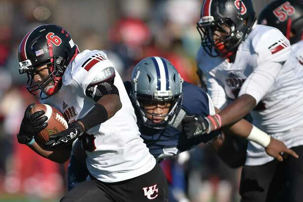 Wilbur Cross running back Jasiah Barnes attempts to avoid a tackle by Hillhouse's Prince Boyd in the Elm City Bowl on Thursday.