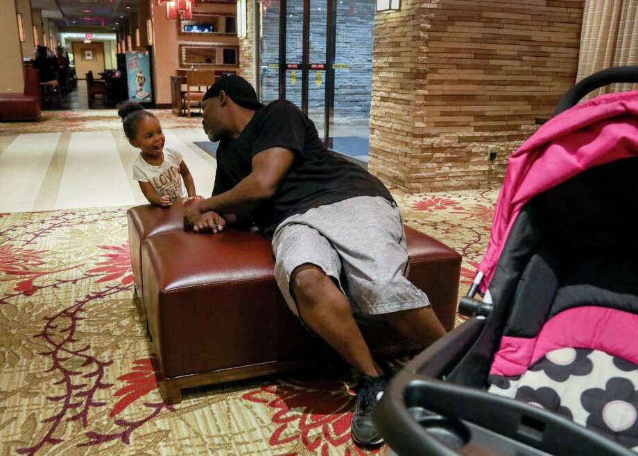 Mikey Robinson, left, talks to his girlfriend's daughter, Nori Nolan, 3, in the lobby of a hotel in the Greenspoint area, Wednesday, Nov. 15, 2017, in Houston.  ( Jon Shapley / Houston Chronicle ) Photo: Jon Shapley, Staff Photographer / Houston Chronicle / © 2017 Houston Chronicle