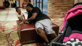 Mikey Robinson, left, talks to his girlfriend's daughter, Nori Nolan, 3, in the lobby of a hotel in the Greenspoint area, Wednesday, Nov. 15, 2017, in Houston.  ( Jon Shapley / Houston Chronicle )