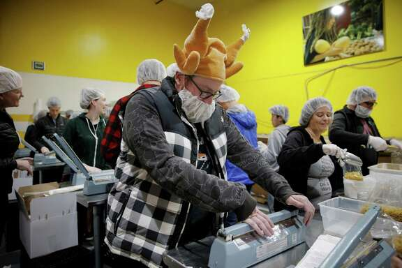 Clinton Karr seals the bags of pasta, joining the many volunteers who are sorting and packing donations.