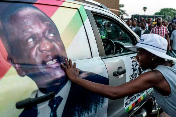 A supporter of Emmerson Dambudzo Mnangagwa touches an image of the new president in Harare on Wednesday. An inauguration ceremony is set for Friday.