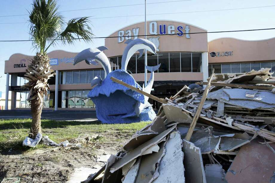 Debris still lines the main streets in front of hotels and businesses like the Bay Quest store as Port Aransas residents gather at Billy Joe's Craft House for Thanksgiving Dinner November 22, 2017 Photo: Tom Reel, Staff / San Antonio Express-News / 2017 SAN ANTONIO EXPRESS-NEWS