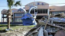 Debris still lines the main streets in front of hotels and businesses like the Bay Quest store as Port Aransas residents gather at Billy Joe's Craft House for Thanksgiving Dinner November 22, 2017