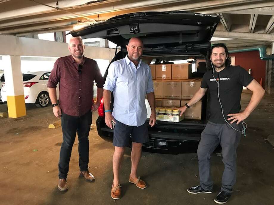 Jonathan Beitler, left, with Lyft, helps driver  Chuck Mullen and Rice University professor Matthew Wettergreen load food for first responders being picked up at the Midtown Kitchen Collective. Photo: Photo Courtesy Lyft