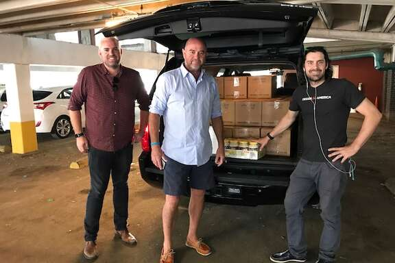 Jonathan Beitler, left, with Lyft, helps driver  Chuck Mullen and Rice University professor Matthew Wettergreen load food for first responders being picked up at the Midtown Kitchen Collective.