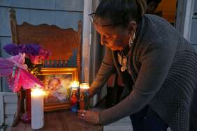 Virgina Ybarbo places candles on a memorial for her great niece Delilah Hernandez,10, who was killed in a shooting, Thursday Nov. 23, 2017 at her home in the 100 block of Harwood Drive.
