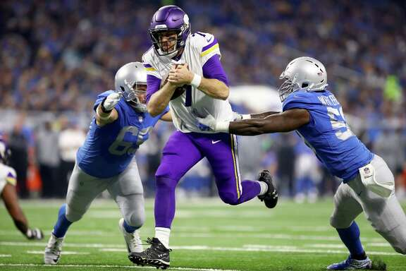 Vikings quarterback Case Keenum splits Lions defenders Anthony Zettel, left, and Tahir Whitehead to score from 9 yards out in the first quarter.