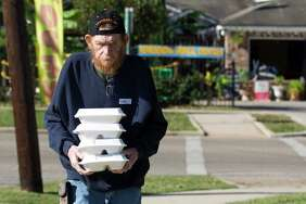 Keith Burkhalt carries meals for neighbors during the annual Thanksgiving Day meal from The Salvation Army and Friends of Conroe, Thursday, Nov. 23, 2017, in Conroe. The event serve 2,500 meals to community members.