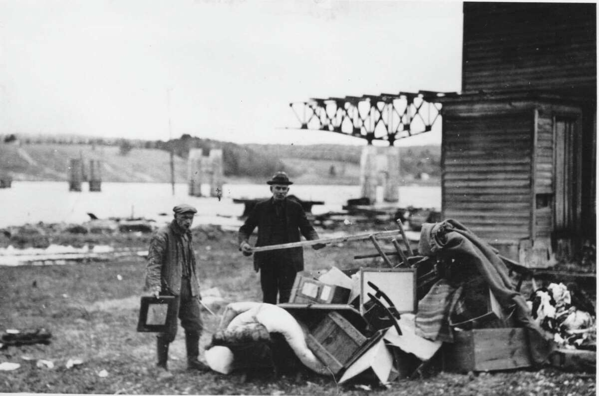 Some homeowners waited until the last minute before they packed up their things and left their homes, structures that would be burned to make way for the Great Sacandaga Lake. The construction of the Batchellerville Bridge is in the background. (Photo: Town of Edinburg Historian)
