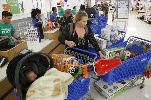 Missy McCauley of Martinez checks out at the Concord Toys R Us, which opened at 5 p.m. on Thanksgiving.