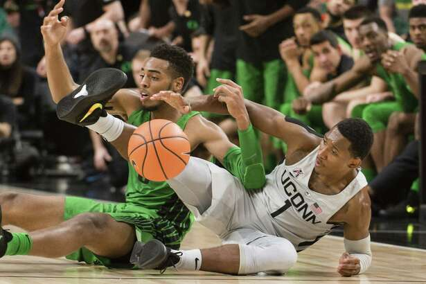 Oregon forward Troy Brown, left, scrambles for a loose ball against Connecticut guard Christian Vital, right during the second half of an NCAA college basketball game at the Phil Knight Invitational tournament in Portland, Ore., Thursday Nov. 23, 2017. (AP Photo/Troy Wayrynen)