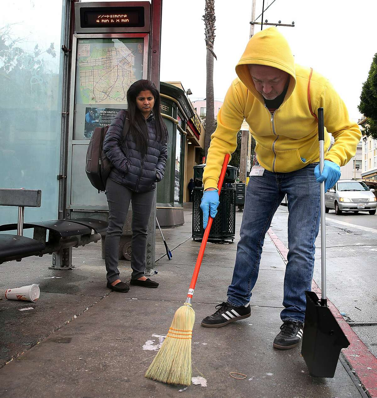 Former supervisor Bevan Dufty sweeps at a bus stop next to the 16th Street bus station on Wednesday, November 15, 2017, in San Francisco, Calif.
