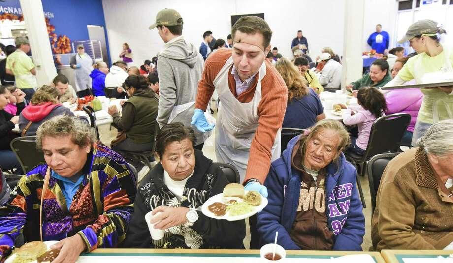 Jonathan Melendez serves Thanksgiving meals to a group of Laredoans on Thursday, Nov. 23, 2017 at Bethany House of Laredo. Photo: Danny Zaragoza, Staff Photographer / Laredo Morning Times / Laredo Morning Times