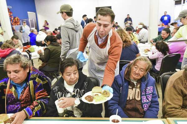 Jonathan Melendez serves Thanksgiving meals to a group of Laredoans on Thursday, Nov. 23, 2017 at Bethany House of Laredo.