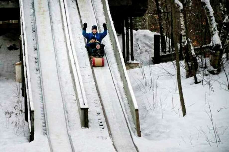 Chuck Carn rides on a toboggan with his sons, Sam, in front, and Logan, at Midland City Forest. (File photo/Neil Blake)