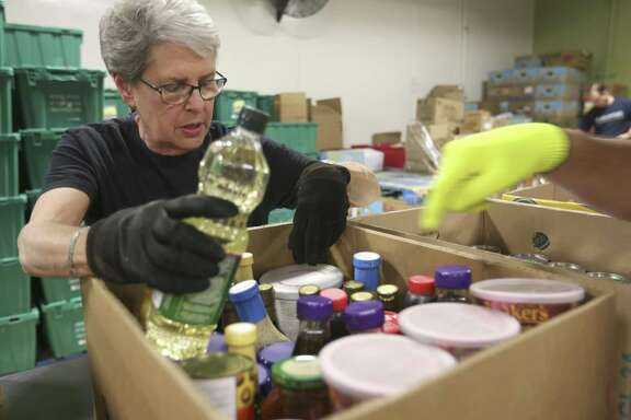 Janet McDaniel, a member of the Apple Corps volunteer group at the San Antonio Food Bank, sorts donated food. She said the work is about more than giving back.