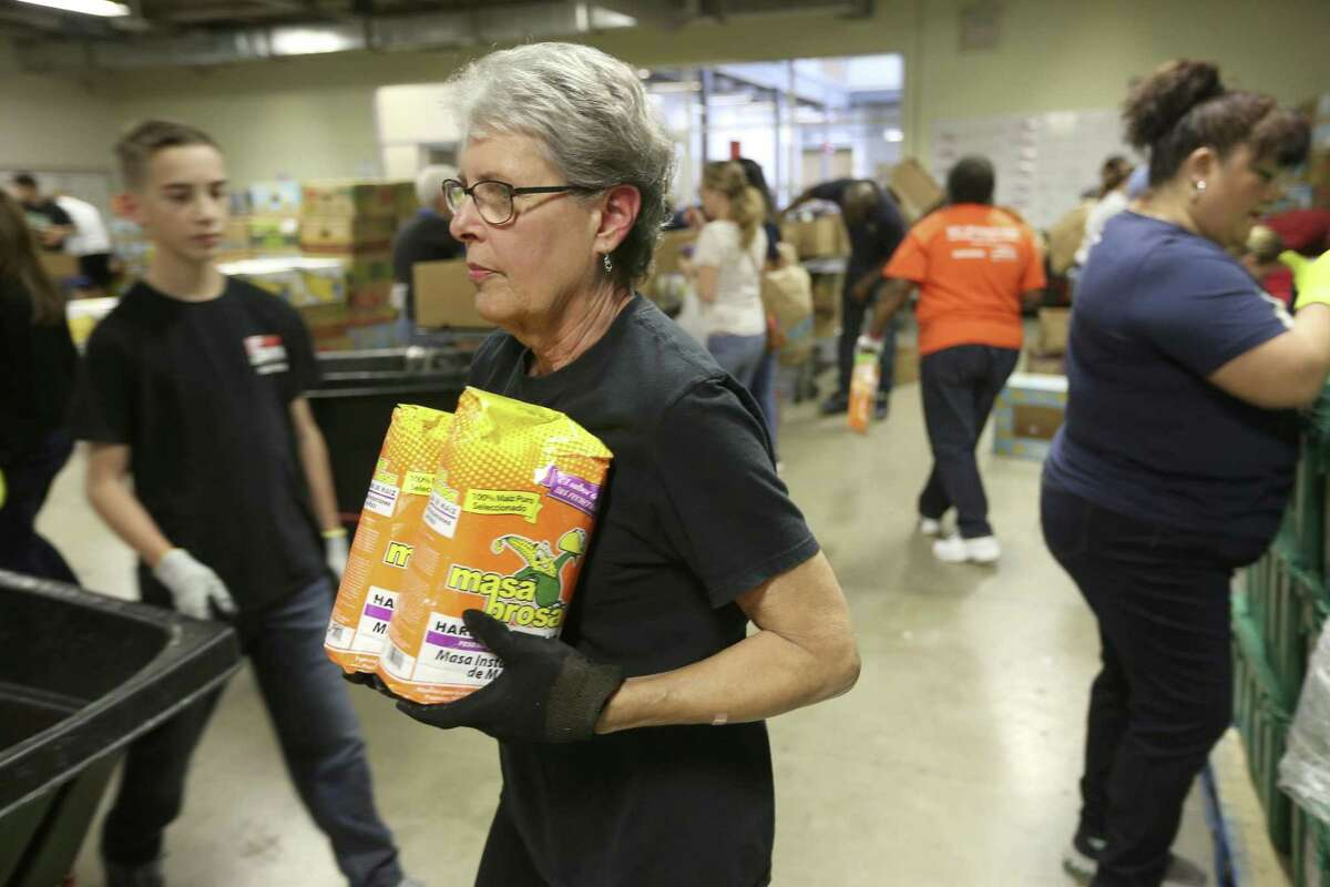 Janet McDaniels, a San Antonio Food Bank volunteer and member of the Apple Corps volunteer group, carries corn meal to an appropriate container as she sorts donated food Nov. 7, 2017