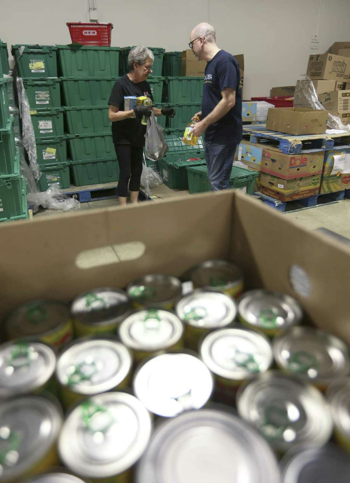 McDaniel helps another volunteer. She says the flexibility makes volunteering at the Food Bank easy.