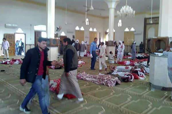 Egyptians walk past bodies following a gun and bombing attack at the Rawda mosque, roughly 40 kilometers west of the North Sinai capital of El-Arish, on November 24, 2017. A bomb explosion ripped through the mosque before gunmen opened fire on the worshipers gathered for weekly Friday prayers, officials said.