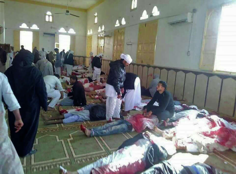 Egyptians walk past bodies following a gun and bombing attack at the Rawda mosque, roughly 40 kilometres west of the North Sinai capital of El-Arish, on November 24, 2017. A bomb explosion ripped through the mosque before gunmen opened fire on the worshippers gathered for weekly Friday prayers, officials said.  / AFP PHOTO / STRINGER        (Photo credit should read STRINGER/AFP/Getty Images) Photo: STRINGER/AFP/Getty Images