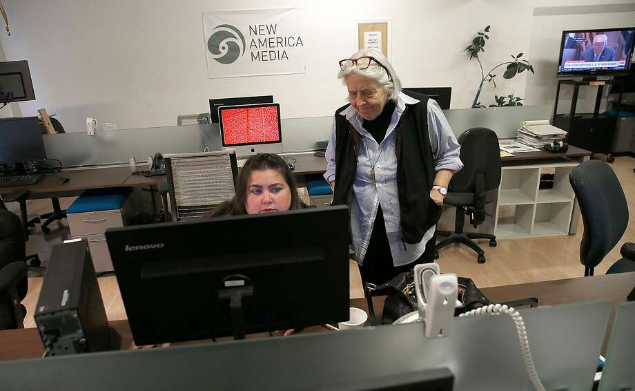 Executive director Sandy Close (right) strolls the offices of Pacific News Service and New America Media. Photo: Liz Hafalia, The Chronicle