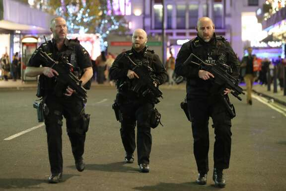 """Armed police patrol near Oxford street as they respond to an incident in central London on November 24, 2017. British police said they were responding to an """"incident"""" at Oxford Circus in central London on Friday and have evacuated the Underground station, in an area thronged with people on a busy shopping day."""