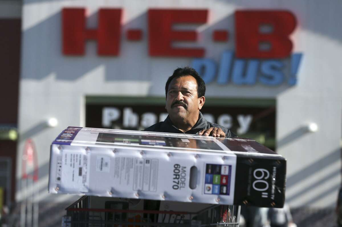 Francisco Serrato hauls a 60 inch Hitachi flat screen T.V. to his car Friday November 24, 2017 at the H-E-B on South New Braunfels on Black Friday.